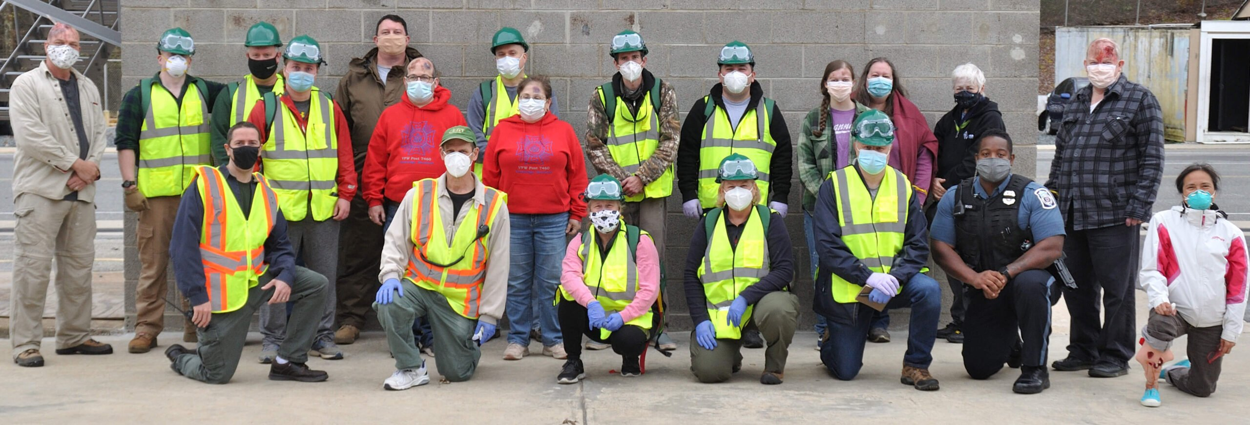 Members of the CERT Basic Class from November 2020 stand with their instructors against a wall at the fire training academy. Trainees are wearing their CERT vests and helmets. All participants are wearing masks.