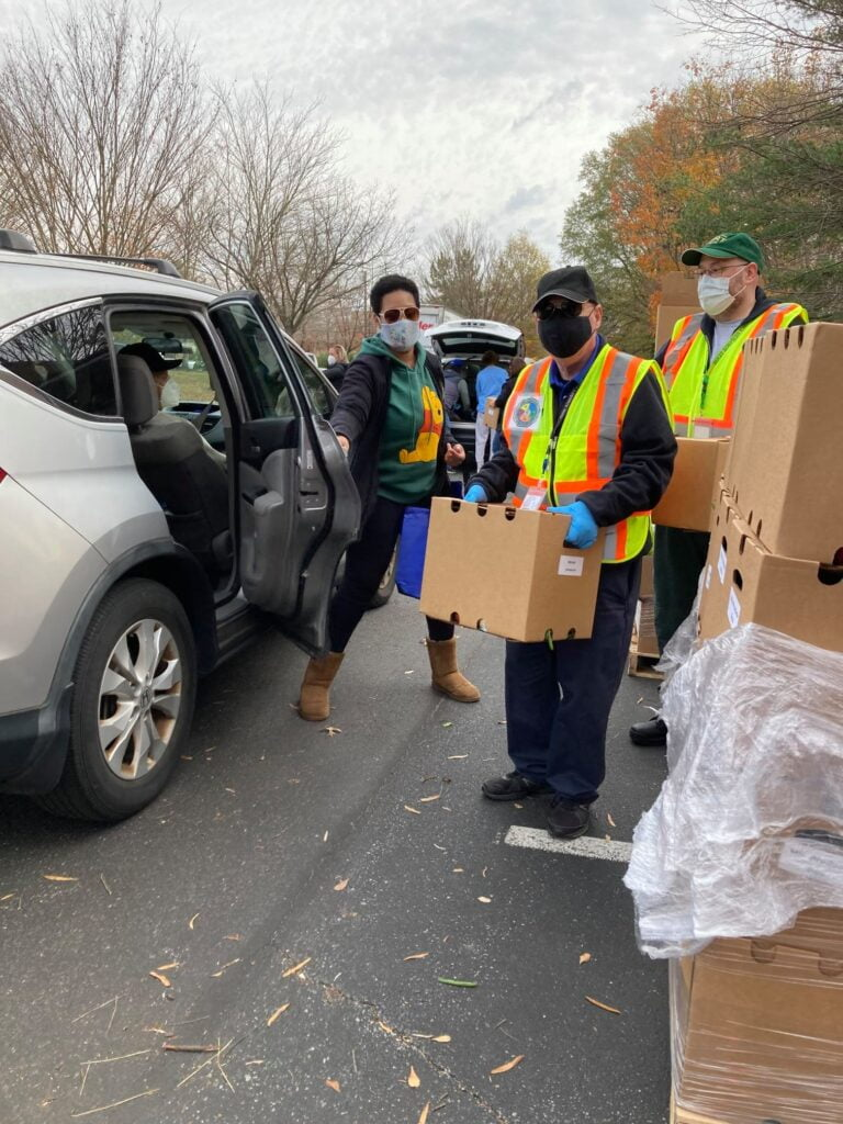 AAACERT member in safety vest holds boxes full of food; a car has pulled up and the door is open to receive food.